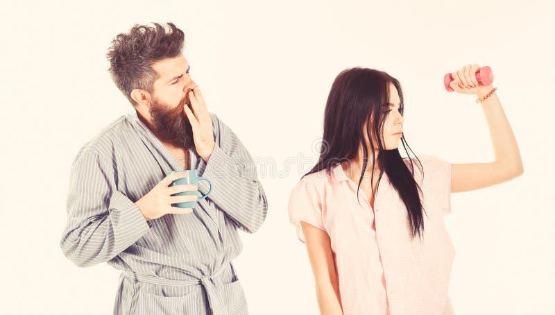 Concetto alternativo di stile di vita Ragazza con la testa di legno, uomo con la tazza di caff? Coppie nell'amore in pigiama, sup fotografia stock