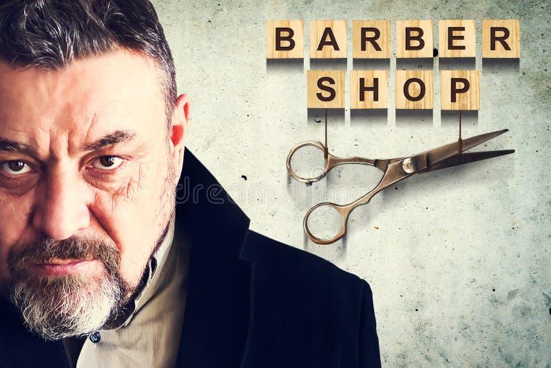 Concetto Barber Shop Uomo barbuto sui precedenti di un muro di cemento Negozio di barbiere dell'iscrizione Bellezza e modo immagine stock