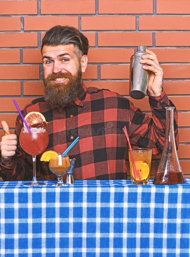 Concetto bevande alcoliche L'uomo in camicia a quadretti su fondo muro prepara da bere Barman con barba lunga e fotografia stock libera da diritti