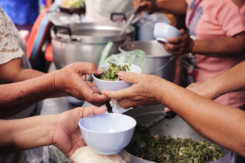 Concetto che affronta fame ed alimento: Doni l'alimento al povero ed al povero che soffrono da inedia fotografie stock libere da diritti