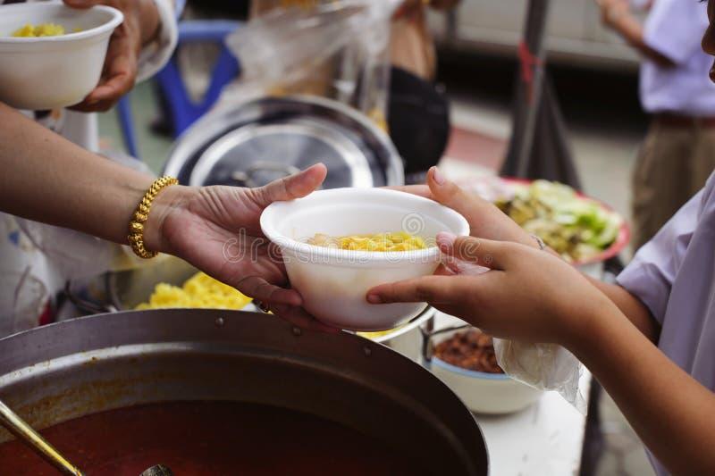 Concetto che affronta fame ed alimento: Doni l'alimento al povero ed al povero che soffrono da inedia fotografia stock