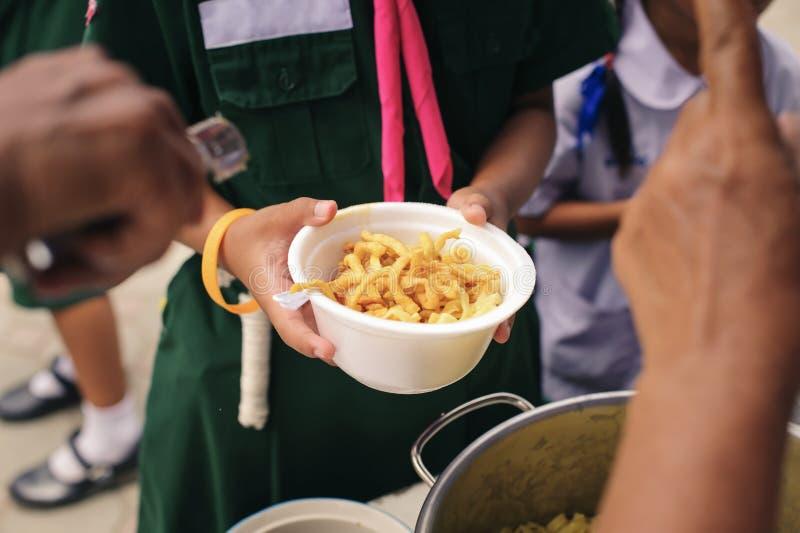 Concetto che affronta fame ed alimento: Doni l'alimento al povero ed al povero che soffrono da inedia immagini stock libere da diritti