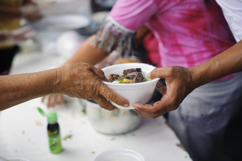 Concetto che affronta fame ed alimento: Doni l'alimento al povero ed al povero che soffrono da inedia fotografia stock libera da diritti
