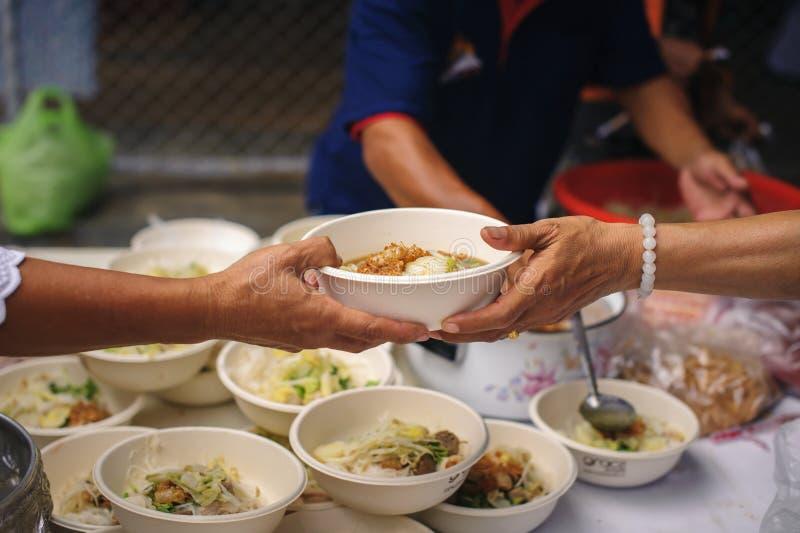 Concetto che affronta fame ed alimento: Doni l'alimento al povero ed al povero che soffrono da inedia immagini stock