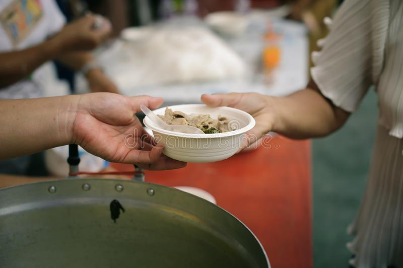 Concetto che affronta fame ed alimento: Doni l'alimento al povero ed al povero che soffrono da inedia fotografie stock