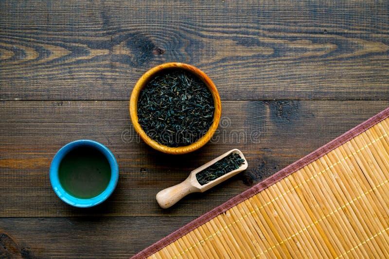 Concetto cinese del tè Cerimonia di tè Foglie di tè asciutte in ciotola e mestolo di legno vicino alla tazza di tè su fondo di le fotografie stock