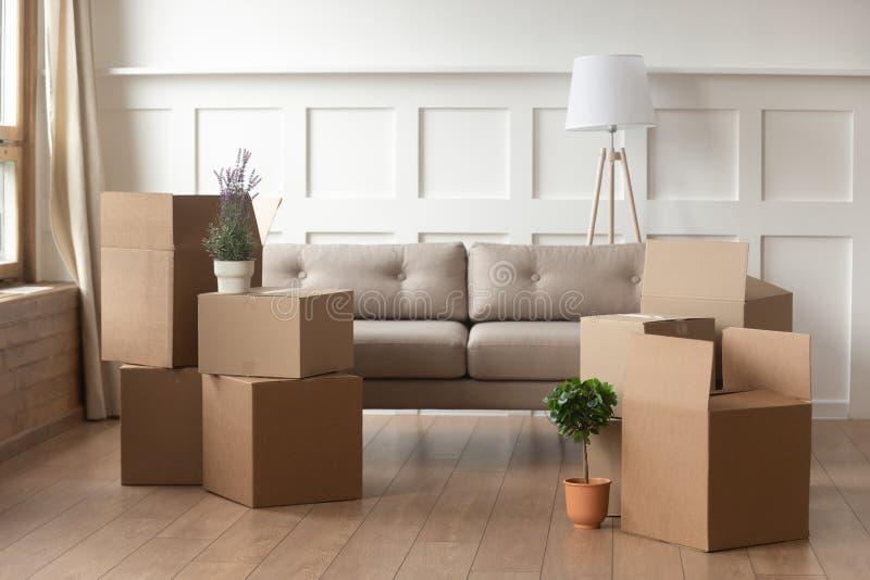 Concetto commovente di giorno, scatole di cartone nel salone moderno della casa immagine stock