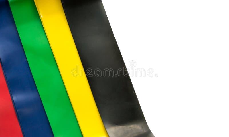 Concetto coperto di erica di stile di vita - estensori elastici della gomma di forma fisica per le donne isolate su fondo bianco  fotografia stock
