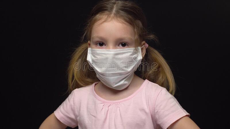 Concetto Coronavirus e inquinamento atmosferico Una bambina indossa una maschera per proteggere Wuhan coronavirus e virus epidemi immagine stock libera da diritti