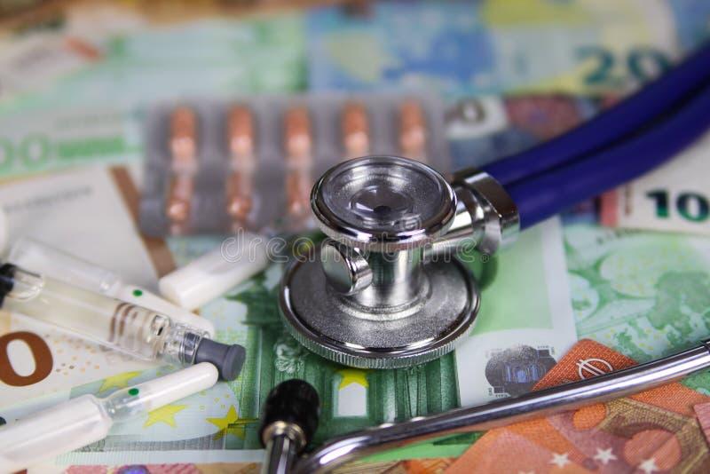 Concetto costato medico - lo stetoscopio, pillole produce delle bolle su ed ampolle sulle euro banconote del biglietto immagini stock libere da diritti