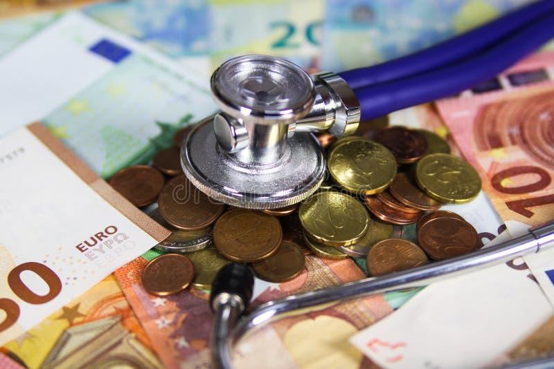Concetto costato medico - stetoscopio sulle euro banconote del biglietto e sulle monete europee fotografia stock libera da diritti