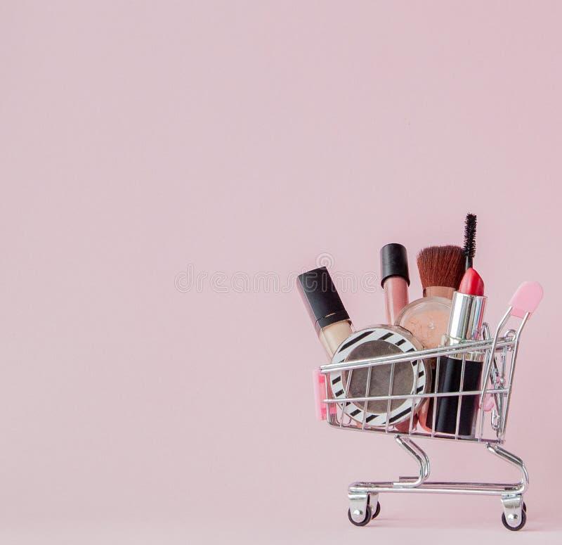 Concetto creativo con il carrello di compera con trucco su un fondo rosa Profumo, spugna, spazzola, mascara, matita, archivio di  immagine stock
