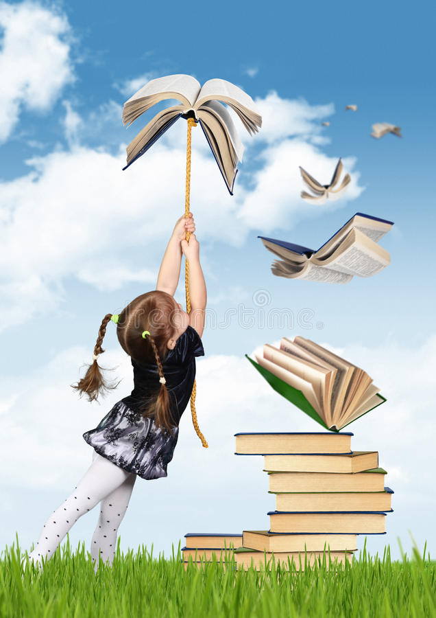 Concetto creativo di istruzione, mosca della ragazza del bambino sul libro immagine stock