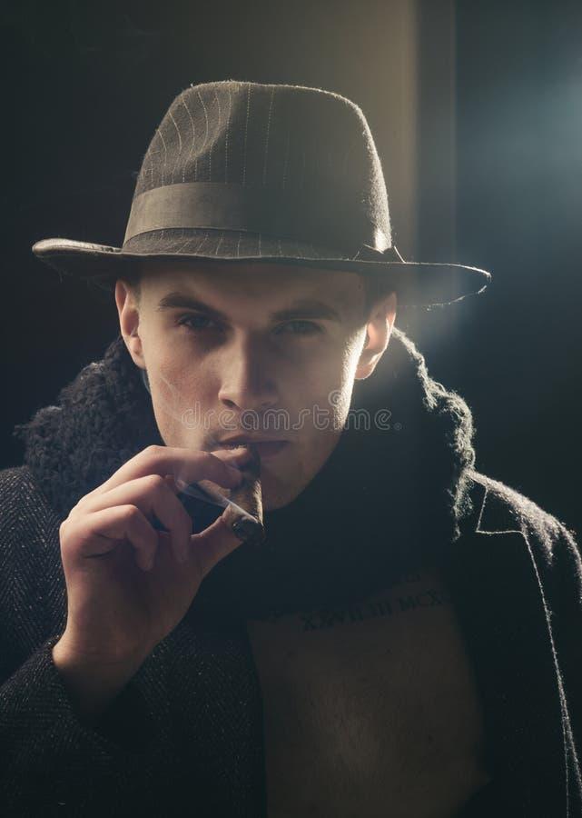 Concetto d'annata dell'agente investigativo Uomo in cappotto, sigaro di fumo del cappello, fondo scuro Macho sul fronte misterios immagini stock