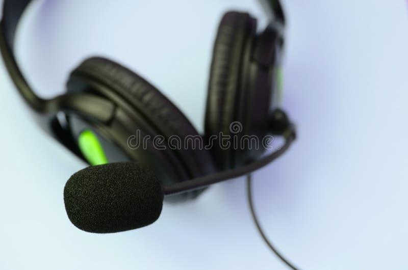 Concetto d'ascolto di musica Bugie nere delle cuffie su fondo blu fotografia stock libera da diritti
