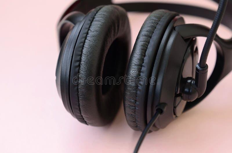 Concetto d'ascolto di musica Bugie nere delle cuffie su fondo rosa fotografia stock libera da diritti