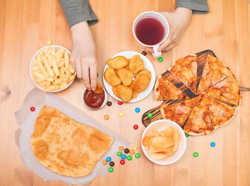Concetto degli alimenti industriali degli alimenti a rapida preparazione Ragazzo teenager che mangia le pepite, pizza, 'chi' fotografia stock libera da diritti