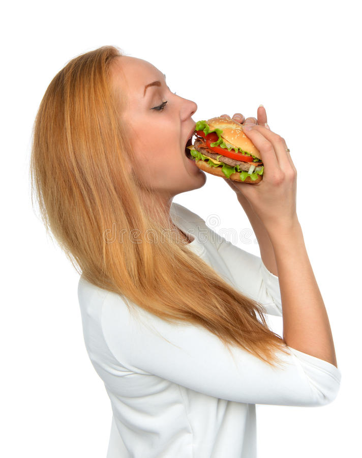 Concetto degli alimenti a rapida preparazione Donna che mangia il panino non sano saporito dell'hamburger fotografia stock