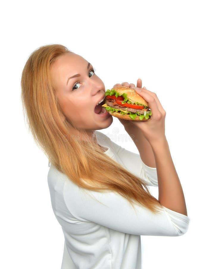 Concetto degli alimenti a rapida preparazione Donna che mangia il panino non sano saporito dell'hamburger fotografie stock