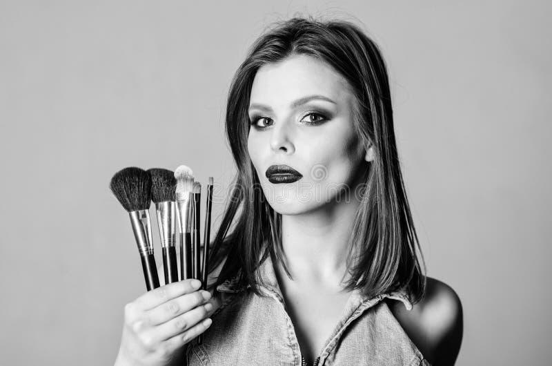 Concetto dei cosmetici di trucco Correttore di incarnato Negozio delle estetiche La ragazza applica gli ombretti Donna che applic fotografie stock