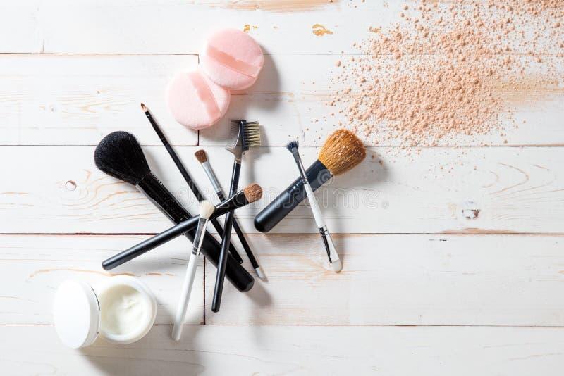 Concetto dei cosmetici e del trucco con polvere, skincare e le spazzole immagine stock libera da diritti