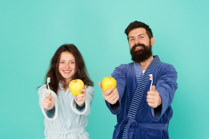 Concetto dei denti della spazzola Igiene orale Accoppi negli spazzolini da denti e nelle mele della tenuta degli accappatoi Igien fotografie stock