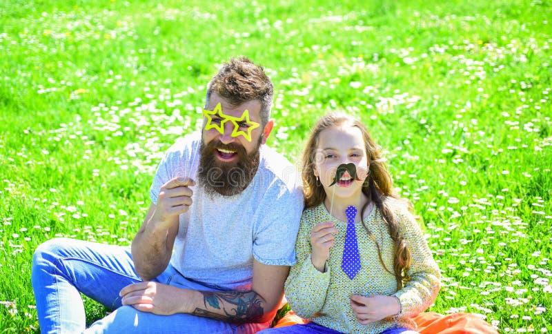 Concetto dei migliori amici Il papà e la figlia si siede su erba a grassplot, fondo verde La famiglia spende lo svago all'aperto fotografia stock libera da diritti