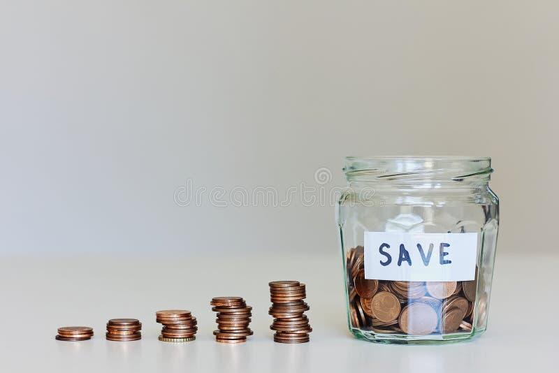 Concetto dei soldi di risparmio Barattolo di vetro in pieno delle monete, delle pile di monete e dei risparmi del segno fotografie stock libere da diritti