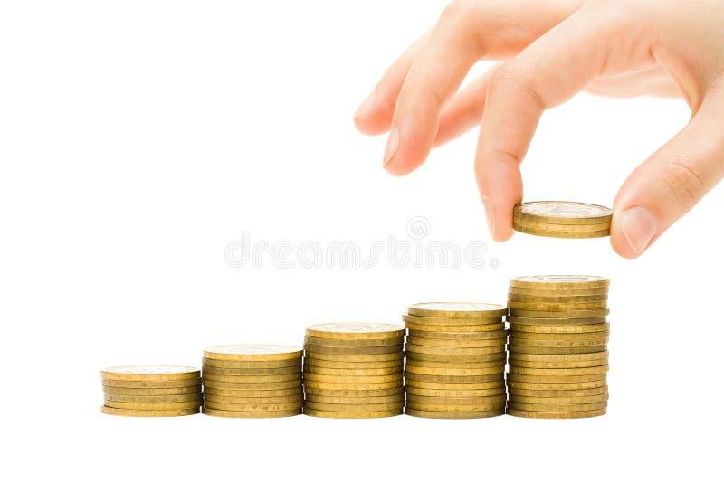 Mano che mette le monete sulle pile dorate dei soldi fotografie stock libere da diritti