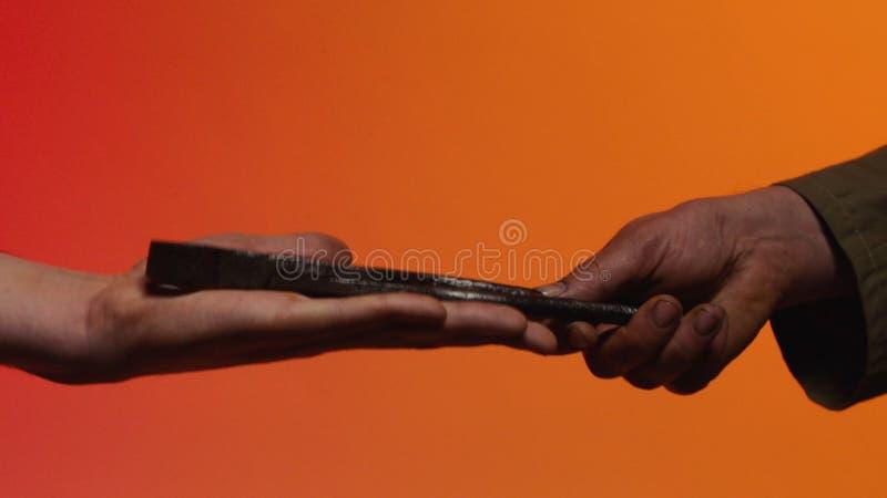 Concetto del baratto azione Il concetto del baratto e della fiducia: la mano umana che dà uno strumento nella mano di un'altra pe fotografia stock