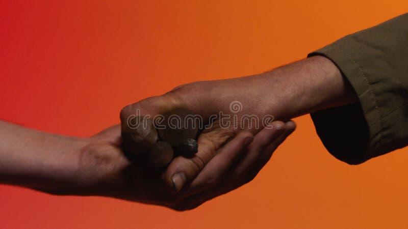 Concetto del baratto azione Il concetto del baratto e della fiducia: la mano umana che dà uno strumento nella mano di un'altra pe immagine stock
