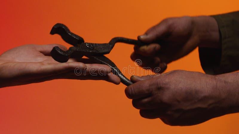 Concetto del baratto azione Il concetto del baratto e della fiducia: la mano umana che dà uno strumento nella mano di un'altra pe fotografie stock libere da diritti