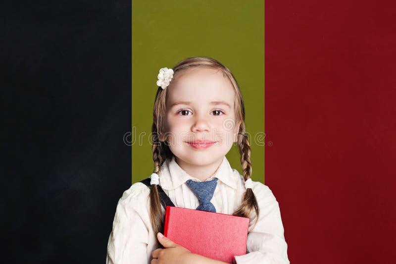 Concetto del Belgio con la ragazza felice del bambino in uniforme scolastico con il libro contro i precedenti belgi della bandier immagini stock libere da diritti
