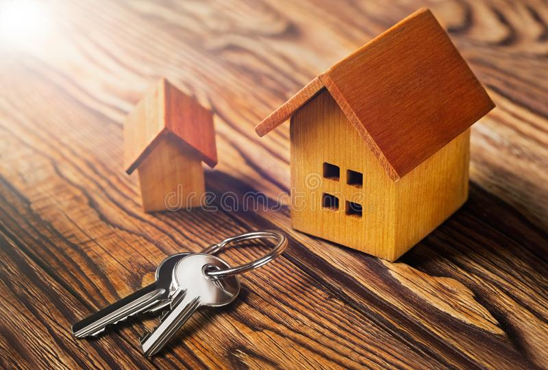 Concetto del bene immobile con la casa di legno del piccolo giocattolo e chiave su fondo di legno Idea per il concetto del bene i immagini stock
