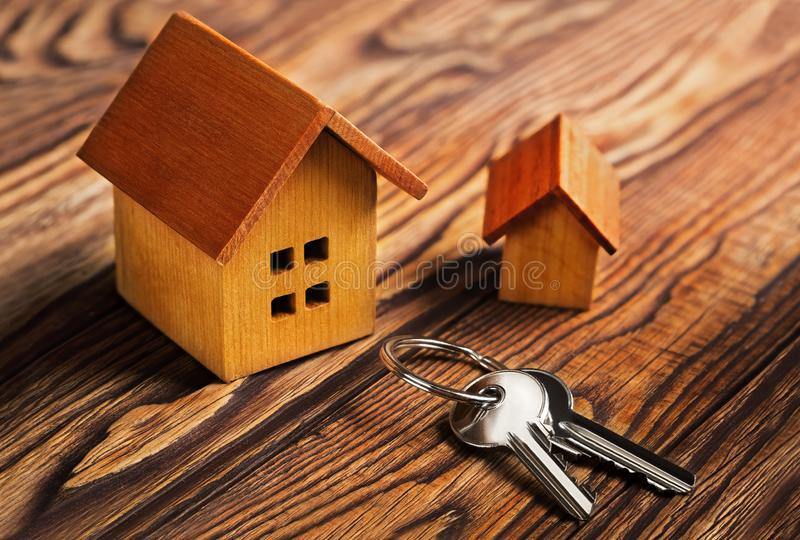 Concetto del bene immobile con la casa e chiave su fondo di legno Idea per il concetto del bene immobile, proprietà personale immagini stock