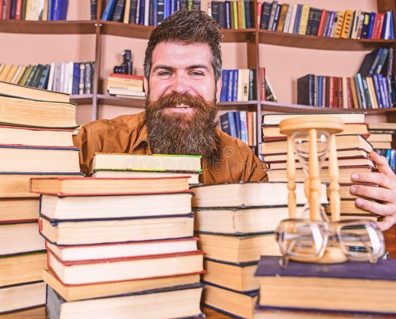 Concetto del bibliotecario L'insegnante o lo studente con la barba si siede alla tavola con i libri, defocused Uomo sul fronte fe fotografia stock libera da diritti