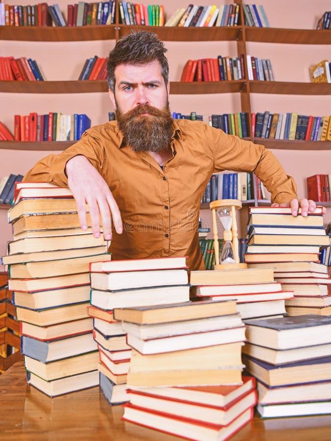 Concetto del bibliotecario L'insegnante o lo studente con la barba sta alla tavola con i libri, defocused Uomo sui supporti premu fotografie stock libere da diritti