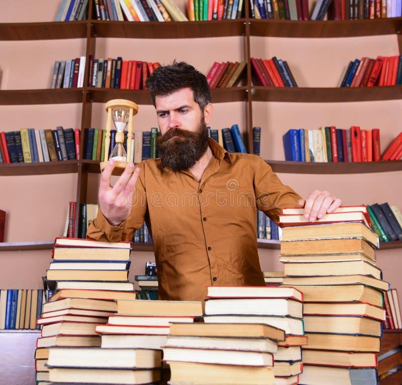 Concetto del bibliotecario L'insegnante, scienziato con la barba sta alla tavola con i libri, defocused Uomo sui supporti premuro fotografia stock