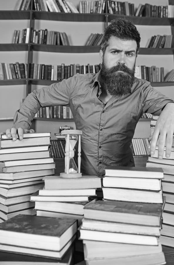 Concetto del bibliotecario L'insegnante, scienziato con la barba sta alla tavola con i libri, defocused Uomo sui supporti premuro fotografie stock