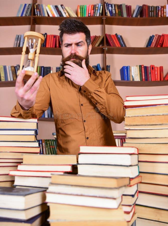Concetto del bibliotecario L'uomo sul fronte premuroso sta fra i mucchi dei libri, mentre tenute clessidra, scaffali per libri so immagine stock