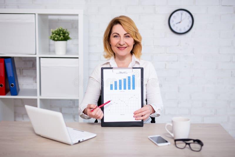 Concetto del business plan - lavagna per appunti allegra di rappresentazione della donna di affari maturi con i grafici ed i graf immagini stock libere da diritti