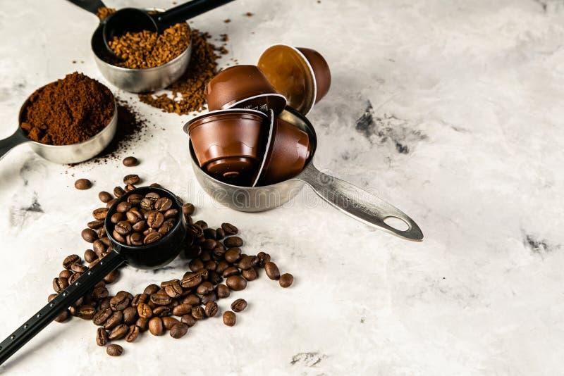 Concetto del caffè - fagioli, terra, istante, capsule, fondo di marmo immagine stock