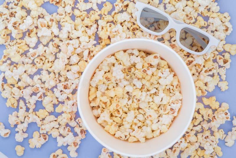 Concetto del cinema Fondo Popcorn, tazza e vetri 3d su un fondo blu pastello immagine stock