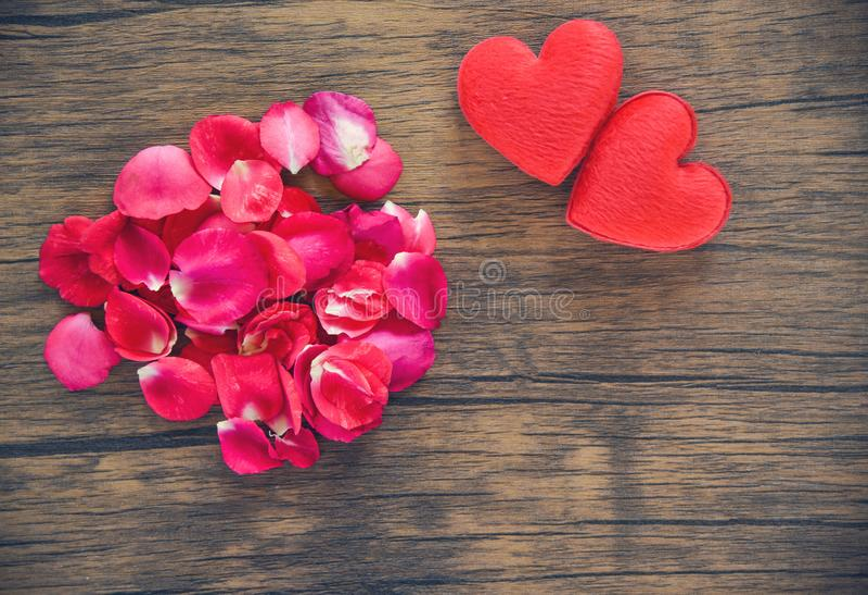 Concetto del cuore di amore di giorno di biglietti di S. Valentino/mucchio dei petali di rose con cuore rosso decorato sulla tavo fotografie stock