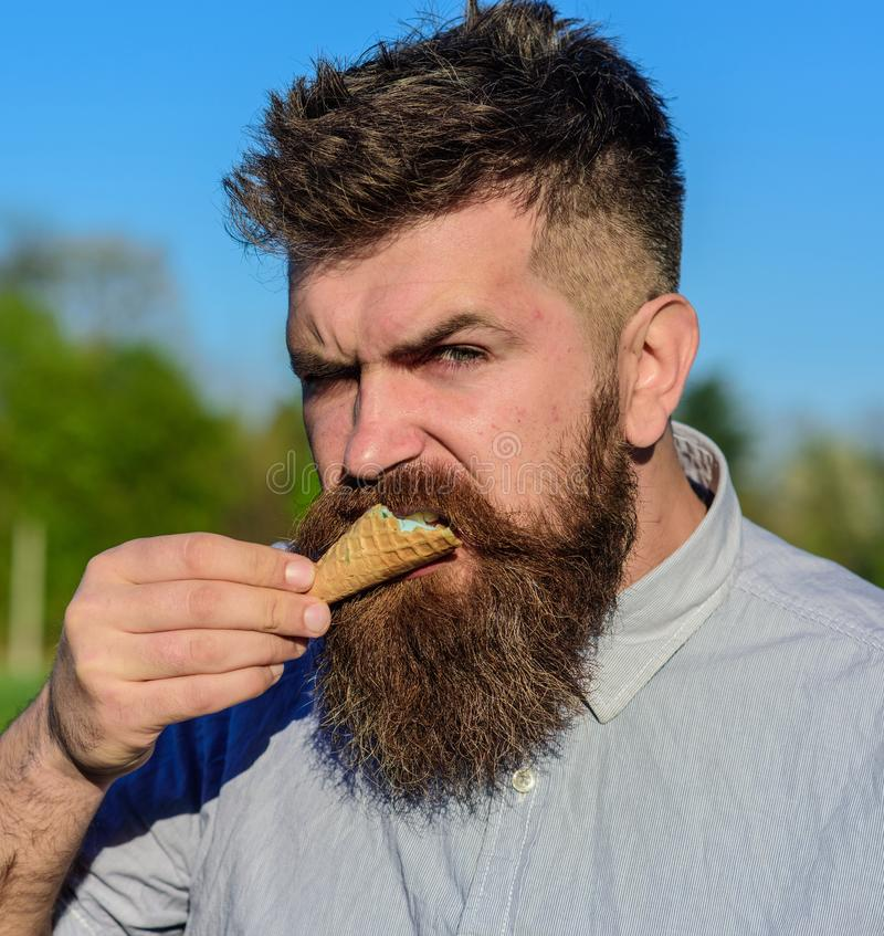 Concetto del dente dolce Uomo barbuto con il cono gelato L'uomo con la barba ed i baffi sul fronte brutale rigoroso mangia il gel fotografia stock libera da diritti