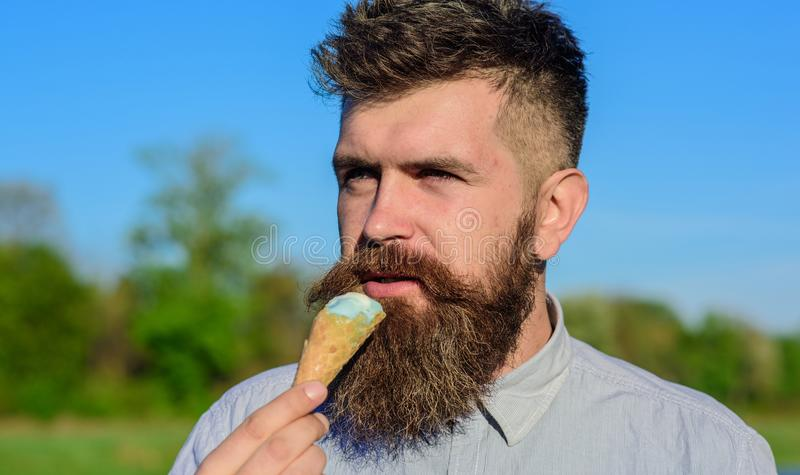 Concetto del dente dolce Uomo barbuto con il cono gelato L'uomo con la barba ed i baffi sul fronte calmo mangia il gelato, morso fotografia stock libera da diritti