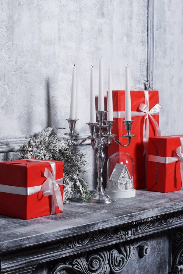 Concetto del fondo di Natale Camino antico con un candeliere ed i contenitori di regalo fotografie stock