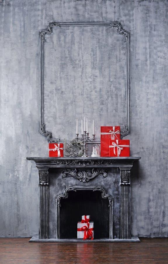 Concetto del fondo di Natale Camino antico con un candeliere ed i contenitori di regalo fotografia stock