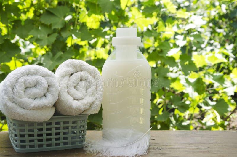 Concetto del lavaggio pulito e morbido Bottiglia di plastica di softner vicino agli asciugamani puliti immagini stock libere da diritti