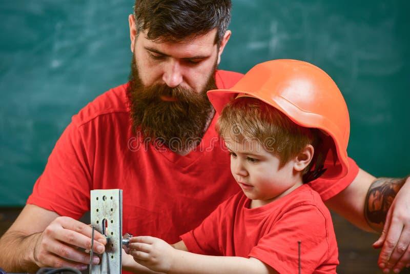 Concetto del lavoro degli uomini Generi con la barba ed il piccolo figlio nell'insegnamento dell'aula per utilizzare gli strument fotografia stock libera da diritti